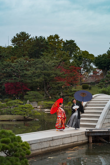 two people smile holding umbrellas on a walkway