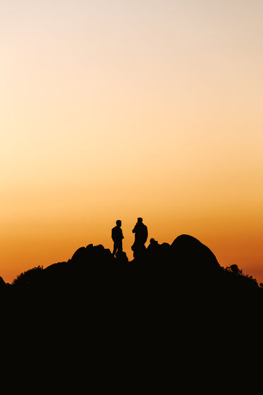 two people stands on a hill silhouetted by the sunset
