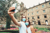 two people take a selfie outdoors while wearing blue facemasks