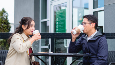 two people take sips from their coffee outside