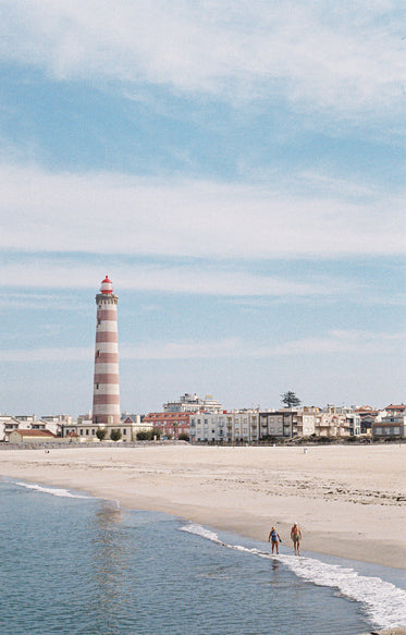 two people walk the beach with a lighthouse in the distance