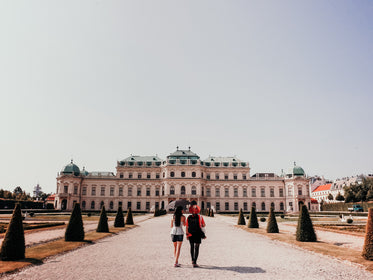 two people walk towards a large white building