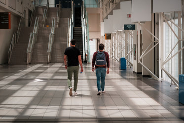 two people walk towards tall stairs in an atrium