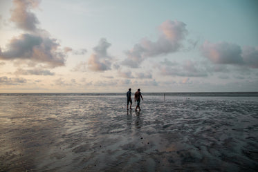 two people walking along the beach at sunset