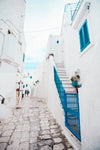 two people walking around white buildings and blue shutters