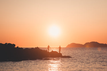 two silhouettes of people fishing at sunset