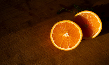 two slices of orange lay on a sunlit cutting board