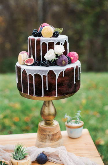 two tier cake decorated with flowers and fruit