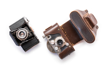 two vintage cameras set on a white background