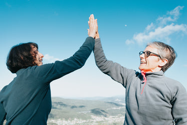 two woman high fiving under blue sky