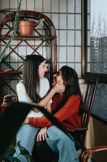 two woman smile as one sits on the other lap
