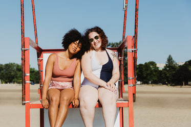 two women sitting on red metal lifeguard chair at beach
