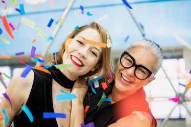 two women smiling in a blizzard of rainbow paper confetti