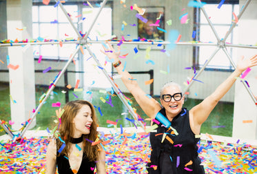 two women surrounded by rainbow confetti with arms raised