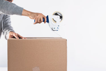 using a tape dispenser to close up a box