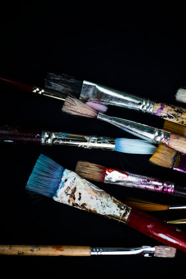 variety of colored paint brushes flatlay on black background