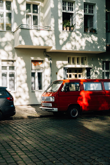 vintage red van parked beside a white building