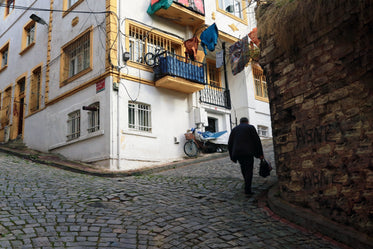 walking up cobblestone street by white and yellow building