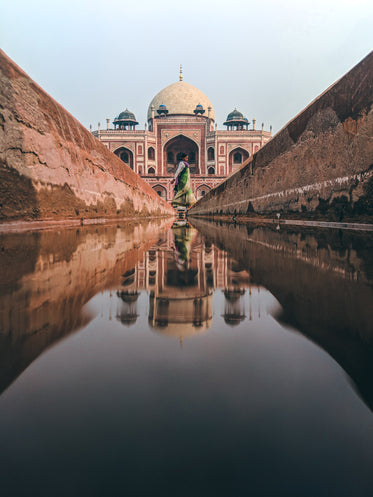 water from a thin canal reflects the taj mahal