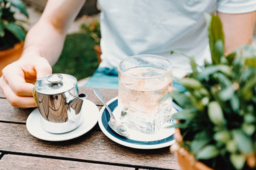 water glass and teapot on an outdoor wood table