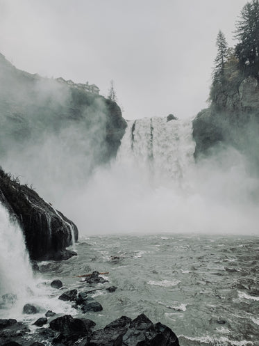 waterfall creating mist over the shore
