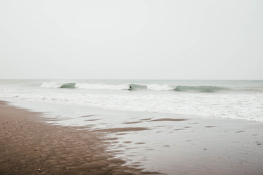 waves roll up to the sandy beach on a overcast day