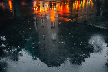 wet pavement reflects a building and city night lights