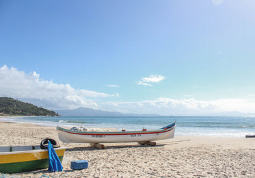 white boat with a red stripe on a sandy beach