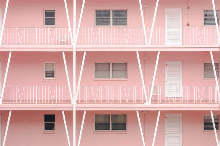 White Doors And Railings In A Pink Apartment Block