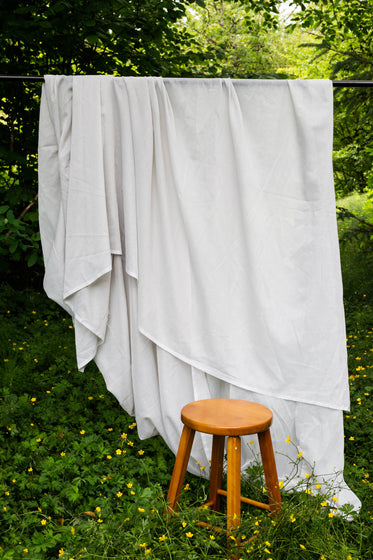 white flowing sheet outdoors with a wooden stool in front of it