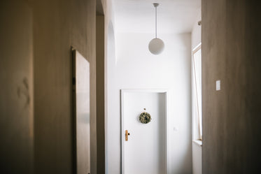 white hallway with a white door and green wreath