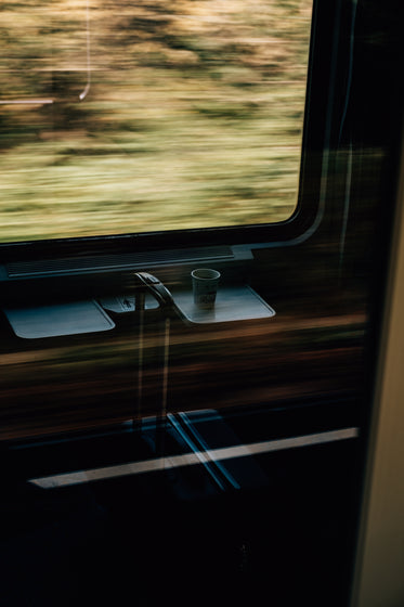 white paper cup and suitcase on a fast moving train