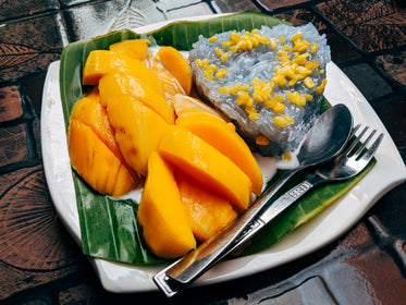white plate with mango rice and cutlery