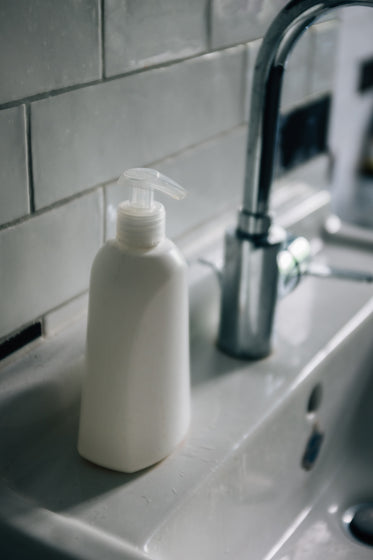white pump bottle sits on a white porcelain sink