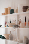white shelves filled with a variety of pottery