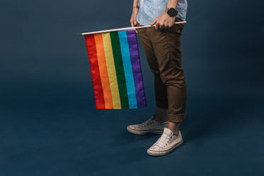 white shoes holding small pride flag