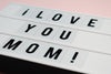 white sign with black text saying i love you mom
