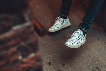white speckled sneakers and dark denim beside brick wall