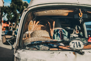 white straw hat sits on a van dashboard