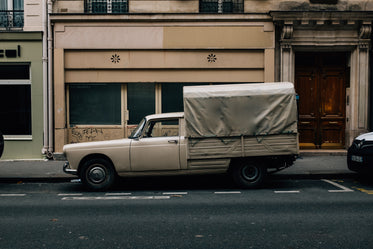 white truck parked outside a large beige building