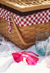 wicker picnic basket with stemless wine glasses