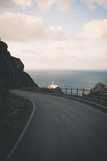 winding paved road with a lighthouse in the distance