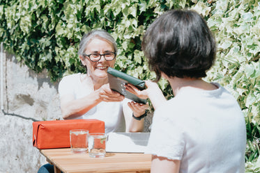 woman accepts a wrapped gift from a friend