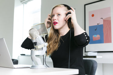 woman adjusting headphones at mic