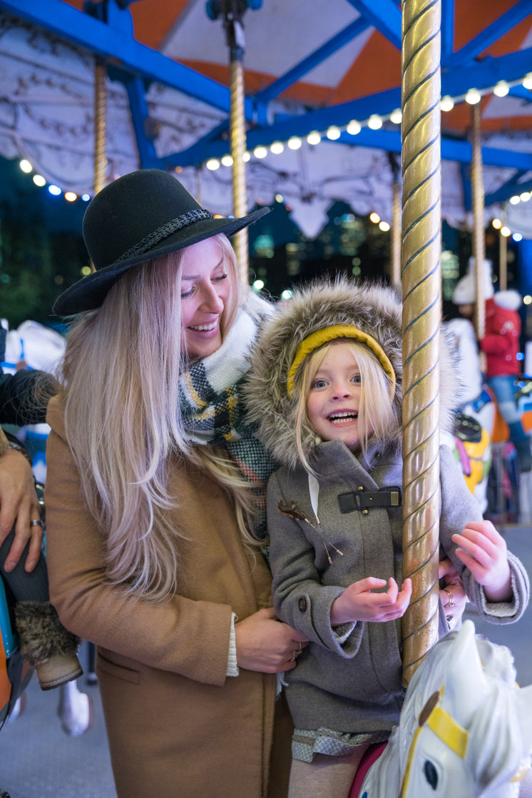 Woman And Girl On Carousel Horse