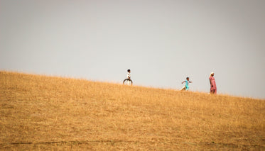 woman and two children stand in a gold colored field