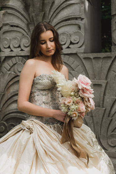 woman bride holding flowers in front of stone wall