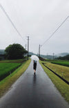 woman carries umbrella along a lonely road