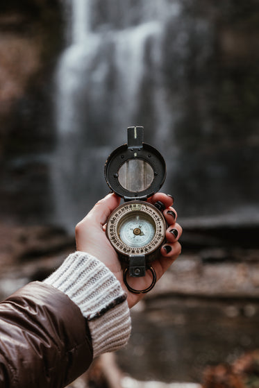 woman checks compass at waterfall