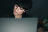 woman concentrates while sitting behind a laptop